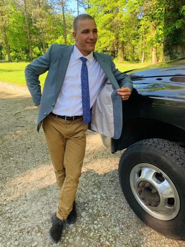 young man wearing suit and khakis leaning on truck